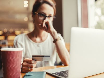 Woman paying her credit card bill online using a laptop but looking worried about the balance remaining.