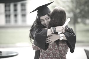 college graduate in cap and gown hugs mother after graduation