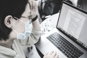 Asian female looking for jobs online using laptop.