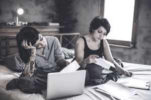 A young couple sits on a bed looking worried as they look at their debts and bills
