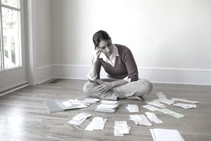 Concerned woman looking at bills and receipts on spread out on the floor around her