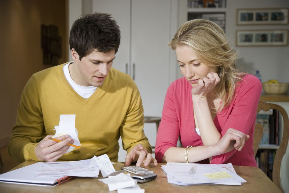 Young couple with receipts and calculator creating a budget