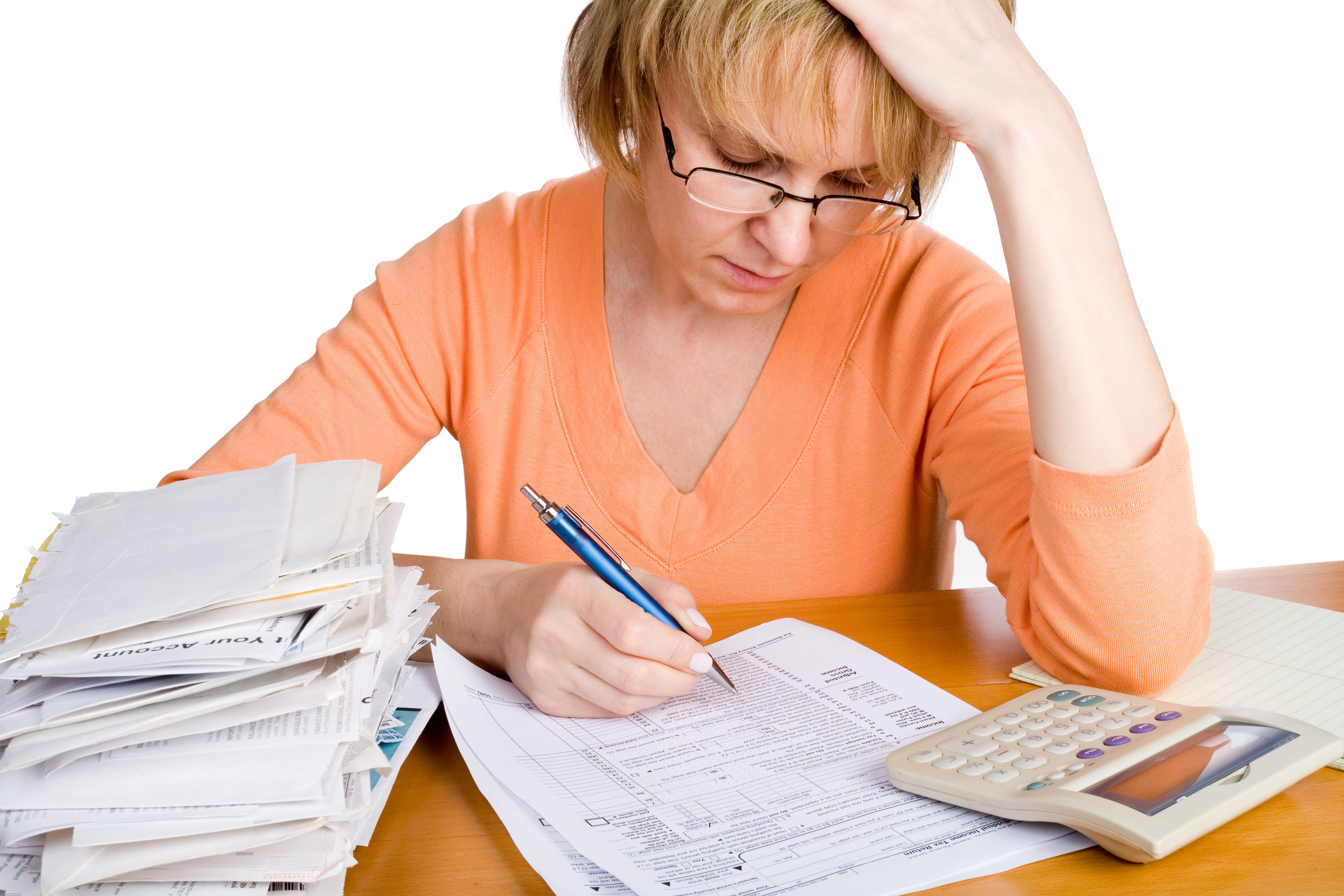 Woman doing her taxes at desk with calculator.