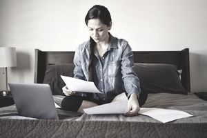 Woman sitting in bed working.